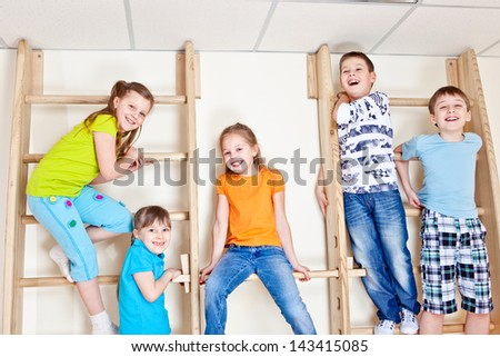 Group of laughing basic school students sitting on wall bars - stock photo