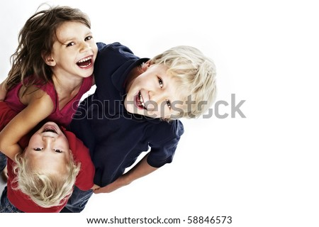 Group of laughing children hugging each other and looking up, isolated on white background with copy-space, top view.