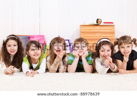Group of laughing children lying in line - stock photo