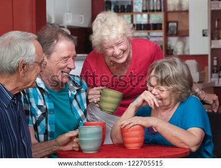 Group of laughing seniors in a coffeehouse - stock photo