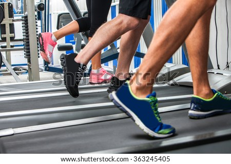 Group of legs wearing sneakers running on treadmill. - stock photo
