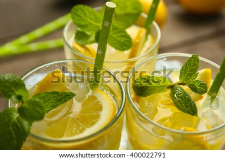 Group of lemonades with lemon and mint view above, closeup