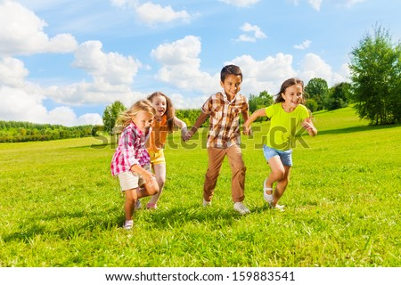 Group of little 6 and 7 years old kids, boys and girls running holding hands together in the park - stock photo