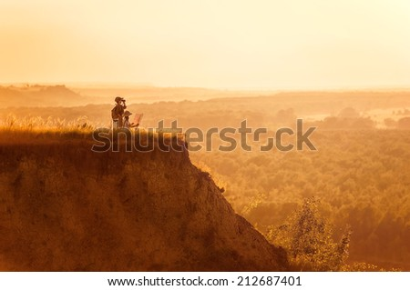 Group of little children, tourists looking into the distance on a high bluff at sunset on a summer evening