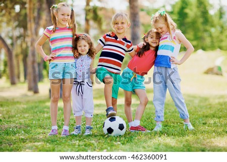Group of little friends playing football in the park