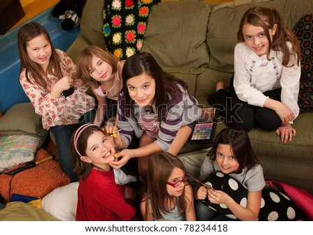 Group of little girls fixing hair and applying makeup - stock photo