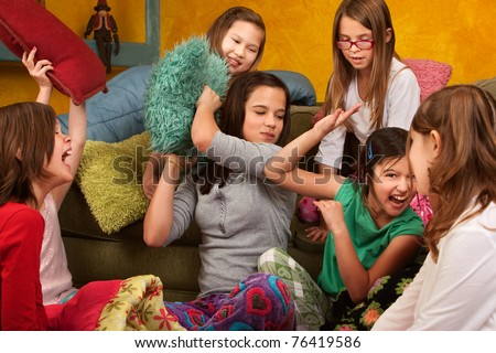 Group of little girls hitting each other with pillows - stock photo