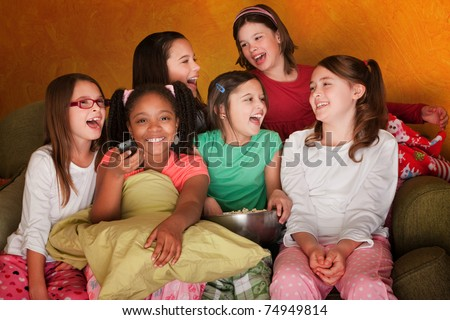 Group of little girls watching television while eating popcorn - stock photo