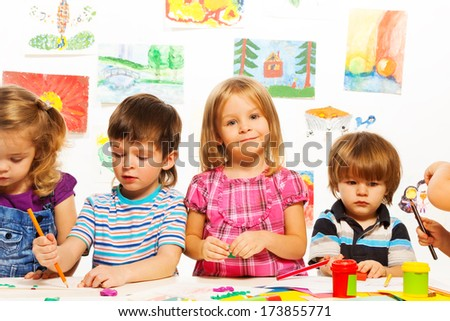 Group of little kids on painting class sitting together with pencils and paints - stock photo