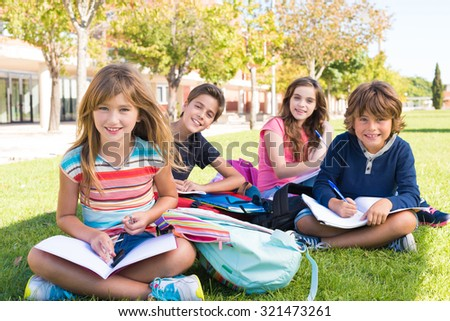 Group of little students sitting on the grass at school - stock photo