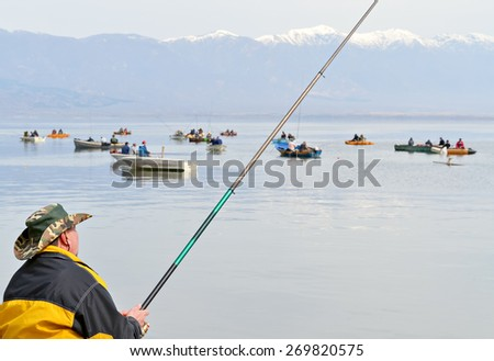 Group of local anglers in their boats fishing in a quiet and cold winter day - stock photo