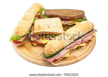 group of long baguette and toasted sandwiches with lettuce, vegetables, salami, ham and cheese on a cutting board isolated on white - stock photo