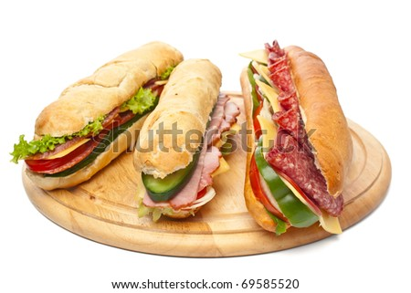 group of long baguette sandwiches with lettuce, vegetables, salami, ham and cheese on a cutting board - stock photo