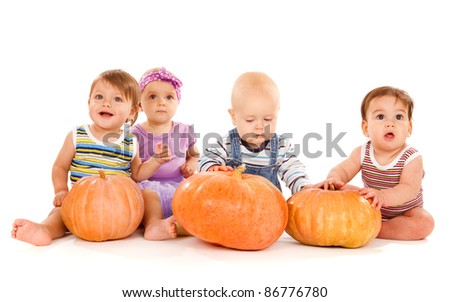 Group of lovely babies with ripe pumpkins, isolated