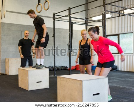 Group of male and female athletes box jumping - stock photo