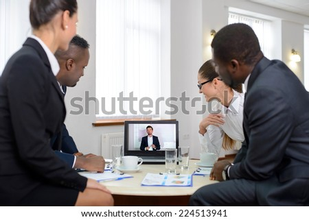 Group of male and female businesspeople seated at a table watching an online conference on a computer screen - stock photo