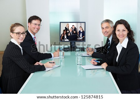 Group of male and female businesspeople seated at a table watching an online presentation on a computer screen