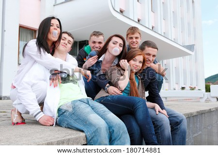 Group of male and female students against the background an academic building - stock photo