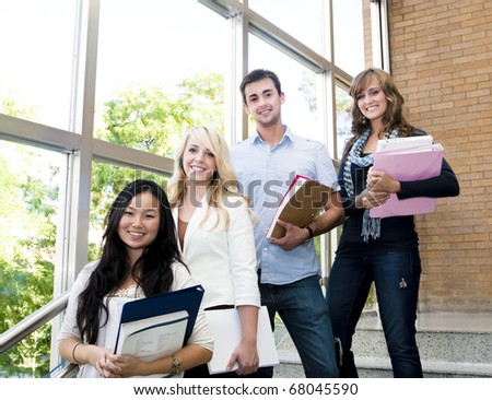Group of male and female students inside an academic building - stock photo