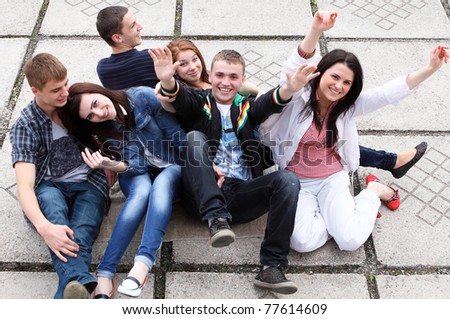 Group of male and female students sitting on street - stock photo