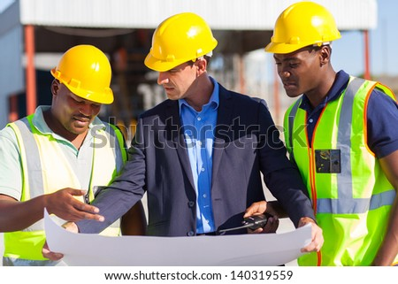 group of male architect and construction workers on construction site - stock photo