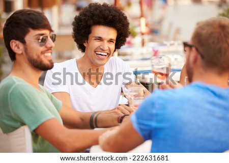 Group Of Male Friends Enjoying Meal In Outdoor Restaurant - stock photo