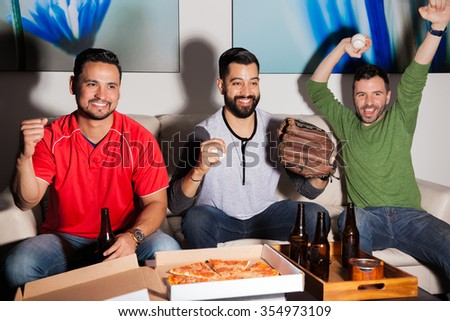 Group of male friends watching a baseball and celebrating a home run from their favorite team - stock photo