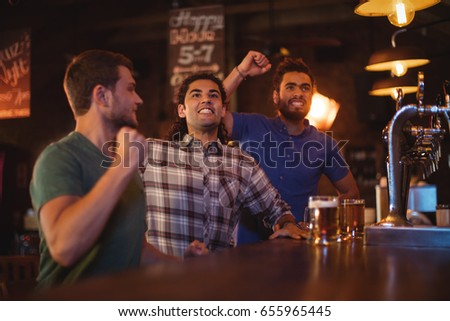 Group of male friends watching football match in pub