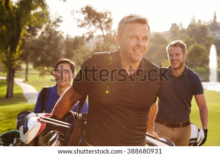 Group Of Male Golfers Walking Along Fairway Carrying Bags - stock photo