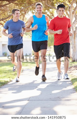 Group Of Male Runners Exercising On Suburban Street