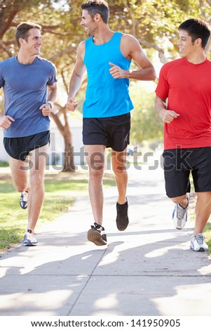 Group Of Male Runners Exercising On Suburban Street - stock photo