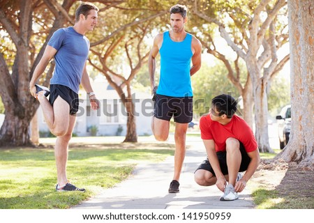 Group Of Male Runners Warming Up Before Run - stock photo