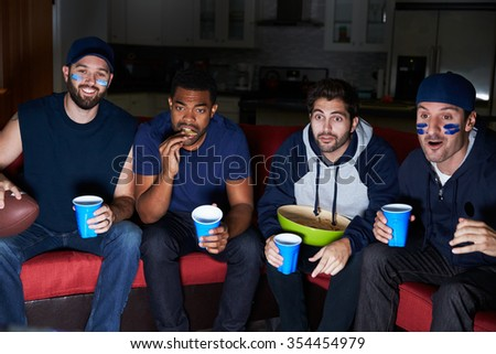 Group Of Male Sports Fans Watching Game On Television - stock photo