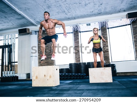Group of man and woman jumping on fit box at gym - stock photo