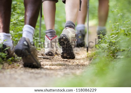 group of man and women during hiking excursion in woods, walking in a queue along a path. Low section view - stock photo