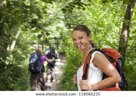 group of man and women during hiking excursion in woods, with woman looking at camera and smiling. Waist up