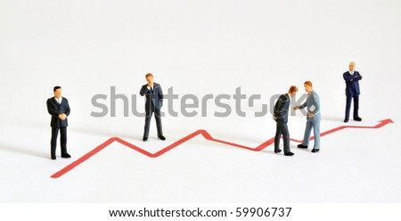 Group of managers (model railroad figures) positioned around graph showing rising development. - stock photo