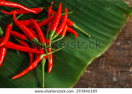 Group of many red chili peppers put on green banana leaf, ingredient of Asian cuisine.