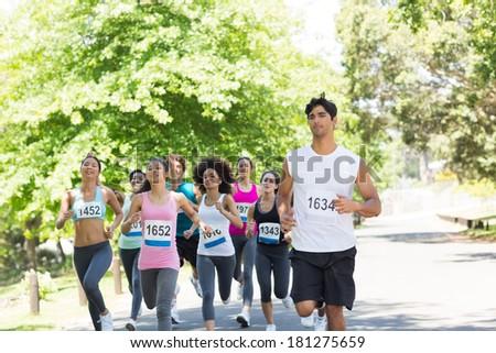 Group of marathon athletes running on street - stock photo