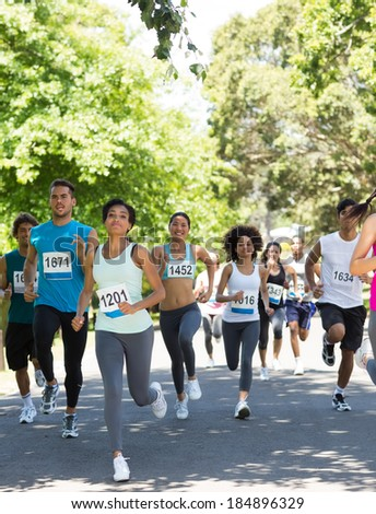 Group of marathon athletes running on street - stock photo