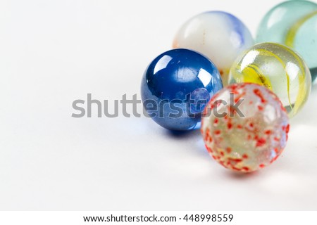 group of marbles in a variety of colors isolated on a white background - stock photo