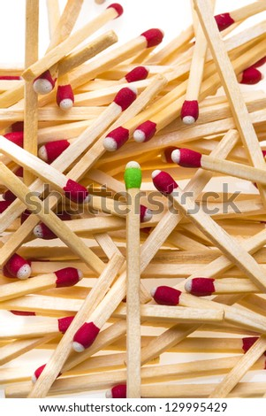 Group of matches with one green match. Representing standing out in a crowd. - stock photo