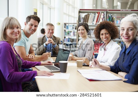 Group Of Mature Students Collaborating On Project In Library - stock photo