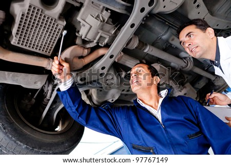 Group of mechanics fixing a car at the garage - stock photo