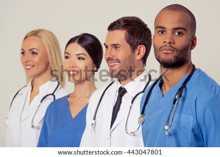 Group of medical doctors of different nationalities and genders is looking forward and smiling, standing in a row on gray background. One is looking at camera