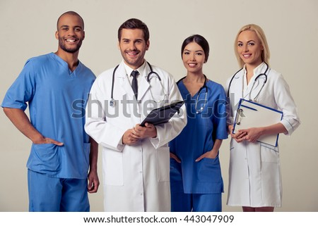 Group of medical doctors of different nationalities and genders with folders is looking at camera and smiling, standing on gray background