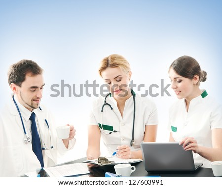 Group of medical workers discussing in office over the blue background - stock photo