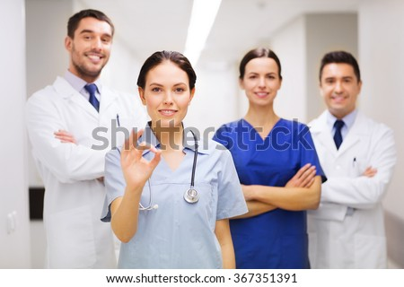 group of medics at hospital showing ok hand sign