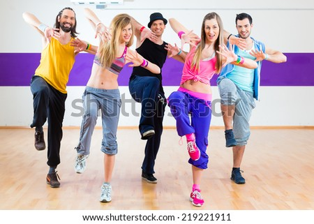 Group of men and women dancing fitness choreography in dance school - stock photo