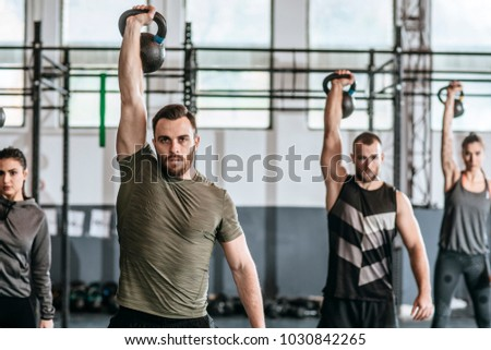 Group of men and women lifting weights at crossfit training at gym.